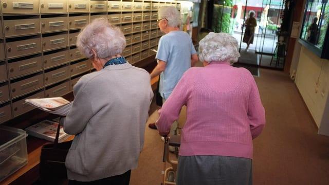 Drei Senioren beim Aussortieren ihrer Post am Eingang des Altersheims Gruenau in Zuerich