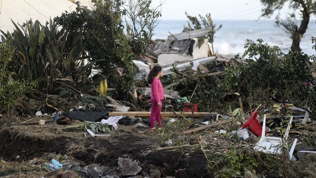 Kind steht inmitten von Trümmern