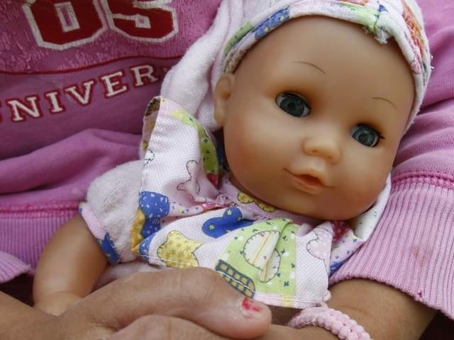 Ein Kind hält eine Puppe im Arm.