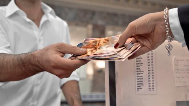 Geld wechselt von einer Hand in eine andere.