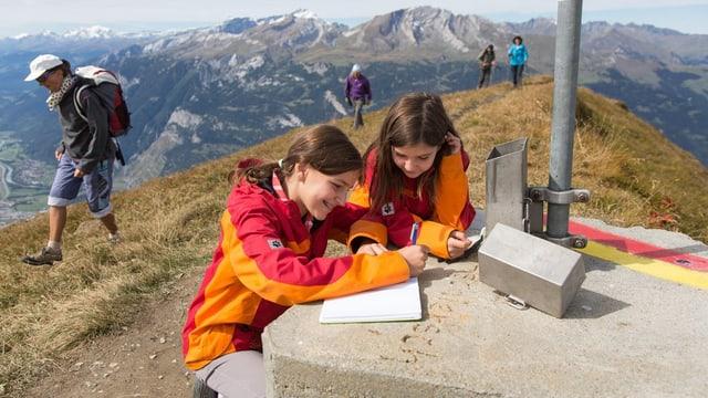 Zwei Mädchen beugen sich auf dem Berg über das Gipfelbuch und machen einen Eintrag.