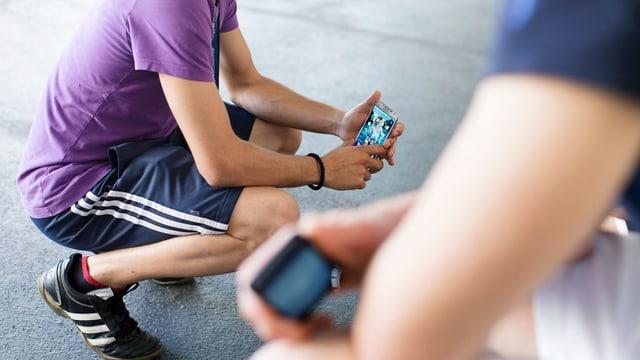 Jungen in Sportsachen, knien mit Handy in der HAnd