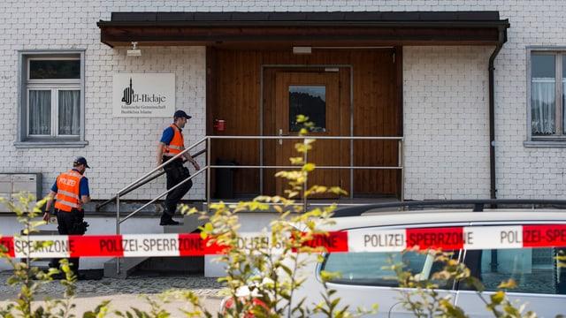 Eine Eingangstür, zwei Polizisten, ein Absperrband.