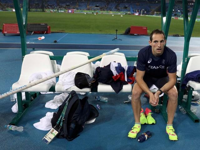 Renaud Lavillenie sitz auf einem Stuhl mitten im Stadion