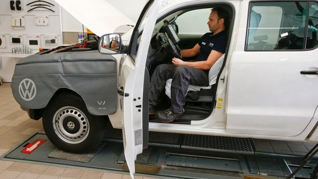 Ein VW auf dem Prüfstand mit offener Wagentür, im Inneren sitzt ein Techniker