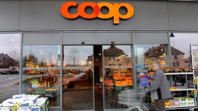 Eingang Coop, Mann mit Einkaufswagen.