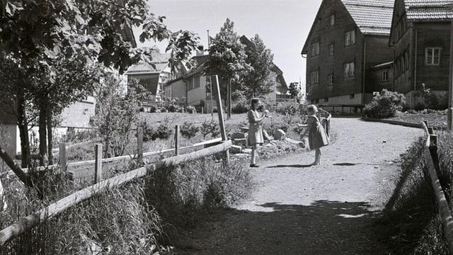eine schwarz-weiss Fotografie von zwei Kindern inmitten Häusern und Garten