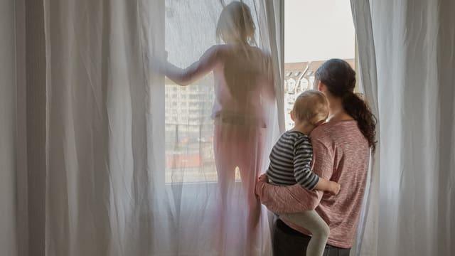 Eine Mutter blickt mit ihren beiden Kindern aus dem Fenster ihrer Wohnung.
