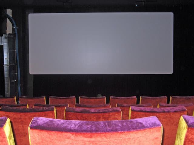 Leinwand im Kino Houdini, im Vordergrund rote Plüschsitze.