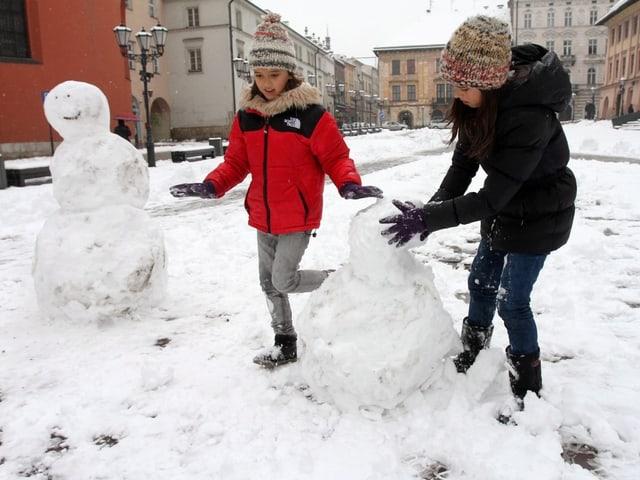 Kinder bauen Schneemänner