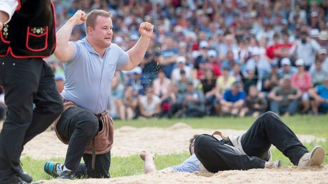 Christian Schuler feiert seinen Festsieg am Innerschweizer Schwing- und Älplerfest Anfang. Er kniet im Sagmehl und hat die Hände erhoben.