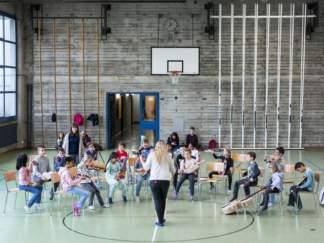 In einer Turnhalle sitzen die Kinder, aufgestellt wie ein richtiges Orchester, mit ihren Papierinstrumenten.