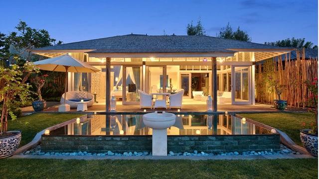 Stattliche Villa im Dämmerlicht mit Pool davor.