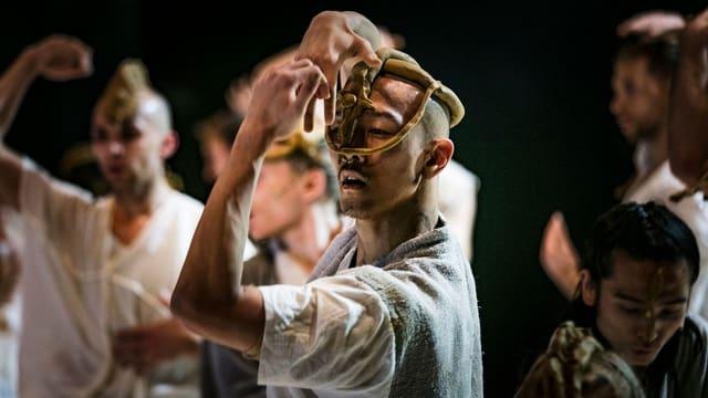 Ein Tänzer mit einer Maske aus goldenen Balken.