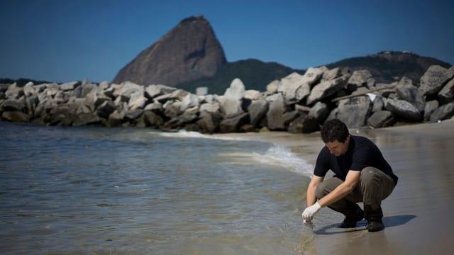 Ein Wissenschaftler nimmt in einer Bucht von Rio eine Wasserprobe.