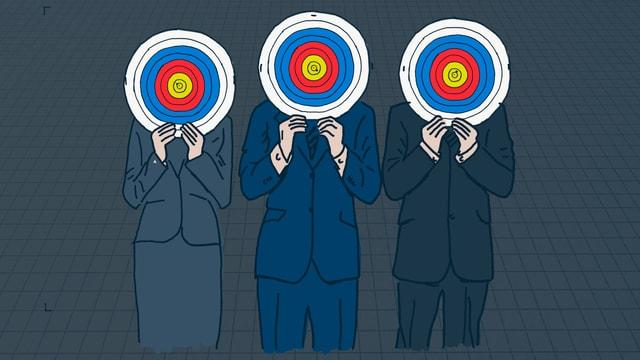 Drei Personen mit Zielscheiben vor dem Kopf