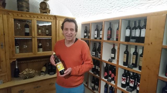 Mario Albin presenta ina buttiglia vin da messa.