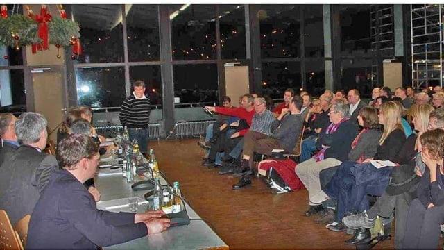 Bürger in einer Turnhalle, am Podium sitzen Vertreter von Gemeinde und Firma