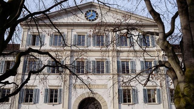 Grosses Haus, viele Fenster mit Bäumen im Vordergrund