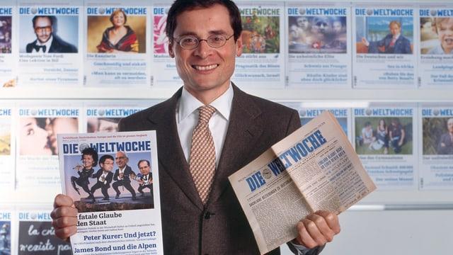 Chefredaktor Roger Köppel hält in seinen Händen Ausgaben der «Weltwoche» von 1933 und 2008.
