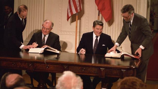 Zwei Männer sitzen vor der amerikanischen und sowjetischen Flagge und unterzeichnen Dokumente