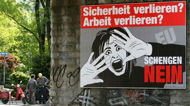 Zwei Männer begutachten eine Vespa hinter der Kulisse eines riesigen Schengen-Nein Plakates.