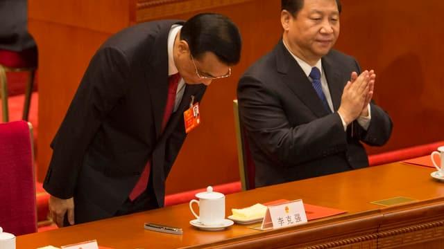 Li Keqiang (l.), sich verbeugend, daneben Xi Jinping applaudierend.