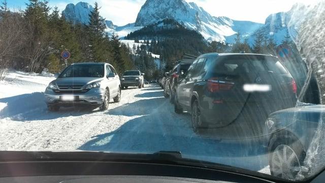 Am rechten Strassenrand parkieren Autos, auf der schneebedeckten Strasse versuchen Autos, zu kreuzen.