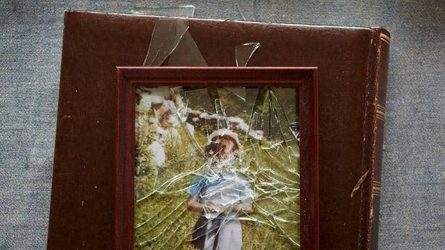 Bilderrahmen mit einer zerschlagenen Scheibe. Darin das Bild eines Kindes, durch die zersprungene Glasscheibe ist das Gesicht nicht zu erkennen.