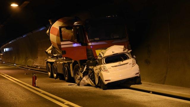 Ein weisses Auto und ein Lastwagen stehen am Strassenrand.