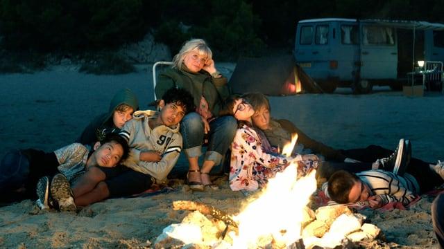 Eine Gruppe von Jugendlichen und eine Frau sitzen am Strand um ein Lagerfeuer herum.