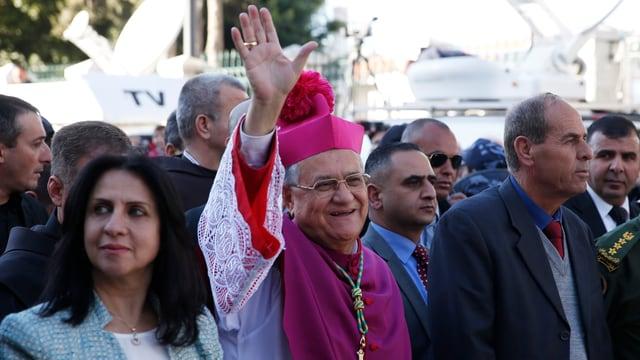 Ein winkender Geistlicher von Gläubigen begleitet