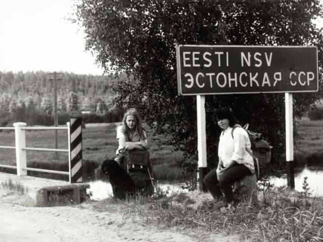 Altes Foto: Zwei Frauen sitzen vor einer Brücke mit Strassenschild.