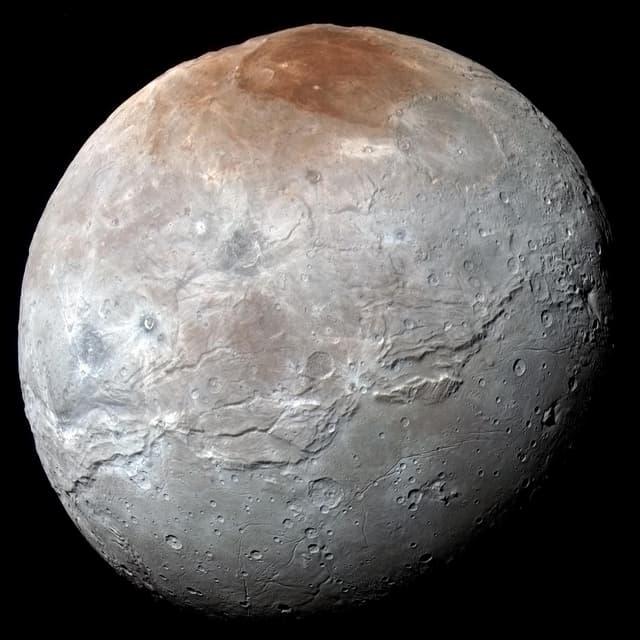 Der Mond Charon auf einem farblich überzeichneten Bild, um die Strukturen auf der Oberfläche zu betonen.