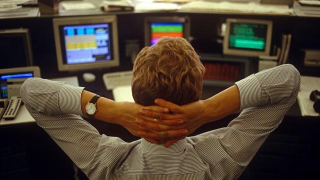 Ein junger Trader sitzt in London vor seinen Bildschirmen mit Börsenkursen, die Hände hinter dem Kopf verschränkt.