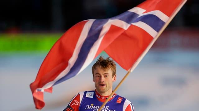 Petter Northug begibt sich mit der norwegischen Fahne auf eine Ehrenrunde.