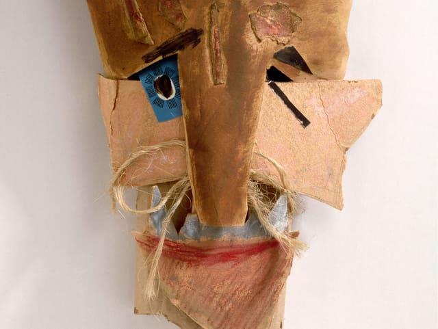 Eine Maske aus Papier, Karton und Farbe, um die Nase hat es Schnüre.