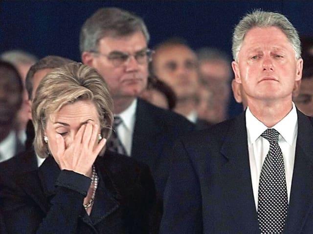 Hillary Clinton reibt sich im Aug. Neben ihr rollt Bill Clinton eine Träne über die Wange.
