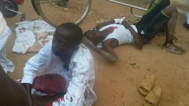 Zwei verletzte Jungen sitzen vor der Schule am Boden.