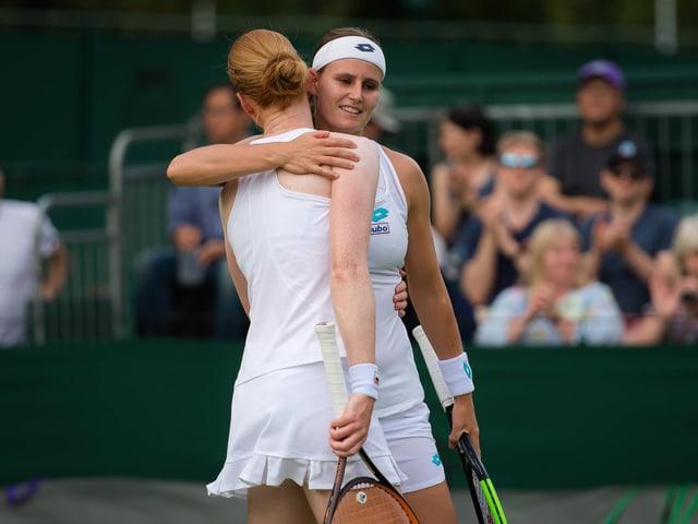 Zwei Tennisspielerinnen umarmen sich.