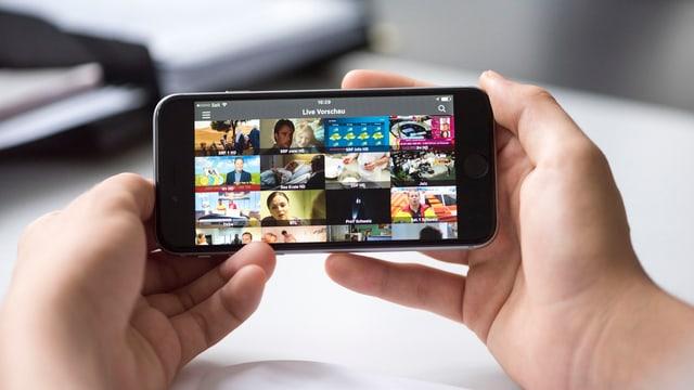 EIne Person hält ein iPhone, auf dem eine TV-Streaming-App läuft.