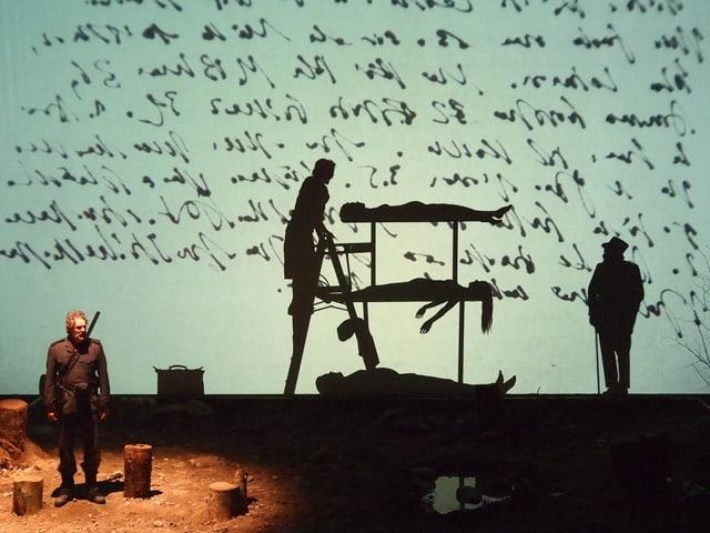 Blick auf die Bühne: Im Scheinwerfer sichtbar ist ein Soldat, hinter ihm als Schattengestalten zwei liegende Frauen und ein Mann und zwei stehende Personen. An den Hintergrund der Bühne ist ein handgeschriebener Text projiziert.