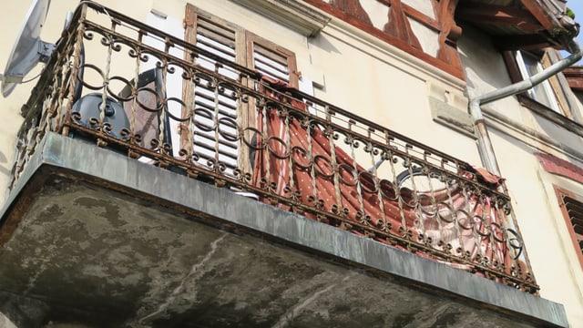 Ein in die Jahre gekommener Balkon mit Metallgeländer von unten fotografiert.
