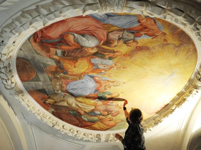 Eine Frau restauriert ein rundes Fresko.