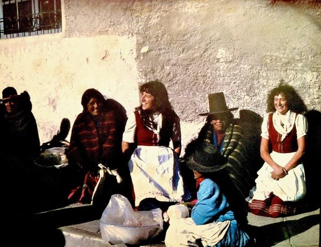 Frauen mit traditionellen bolivianischen Gewändern sitzen auf der Strasse. Mittendrin: Zwei Frauen in