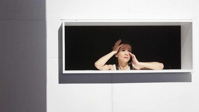 Eine Frau schau aus einem Fenster auf der Theaterbühne.