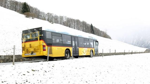 Ein Postauto fährt durch eine verschneite Landschaft.