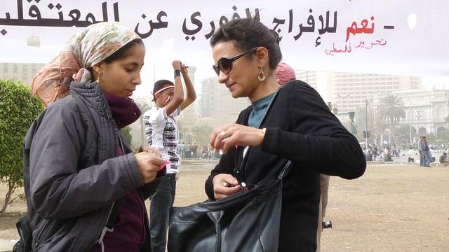 Zwei Frauen, eine trägt Kopftuch, stehen vor einem grossen Banner, der über dem Tahrir-Platz in Kairo gehisst wird.