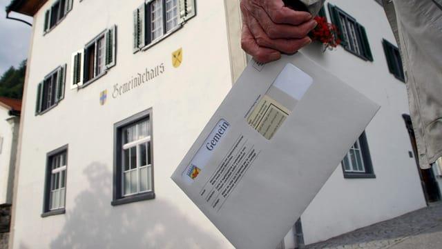 Ein Stimmbrechtigter mit Wahlcouvert vor dem Gemeindehaus.