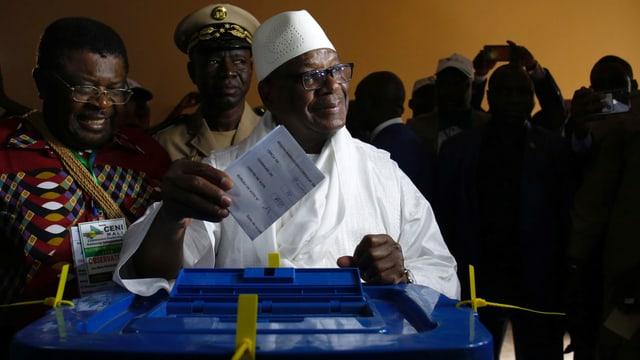 Schwarzer Mann in weisser Tracht wirft Stimmzettel in Urne.
